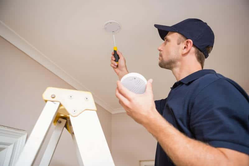 Brisbane southside electrician installing a smoke detector